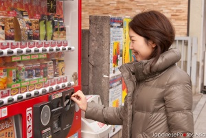 A young Japanese lady using a drink vending machine.