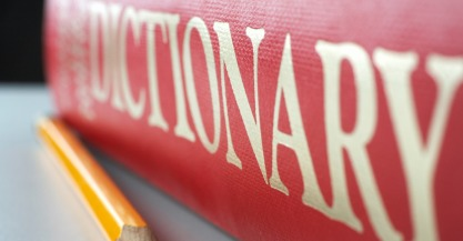 Dictionary and pencil.  Selective focus on the pencil tip.